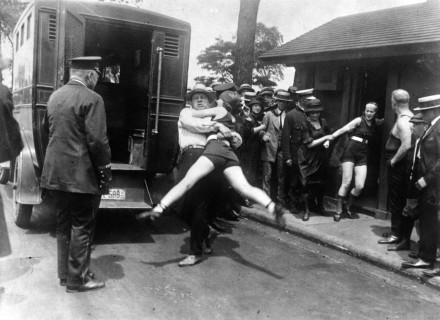 Women in Chicago being arrested for wearing swimsuits that show too much leg, ca. 1922